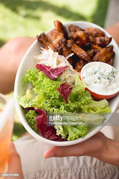 Hands holding chicken wings with blue cheese dip and salad