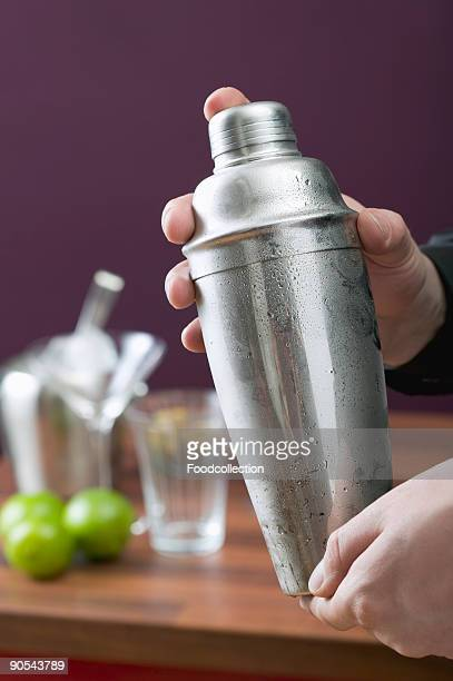 Hands holding cocktail shaker, close up