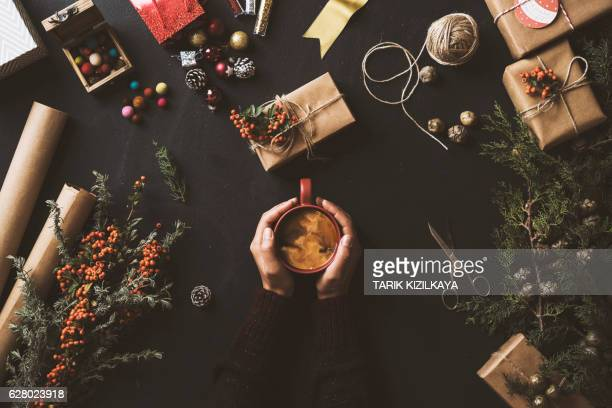 Hands holding coffee, Christmas presents on table