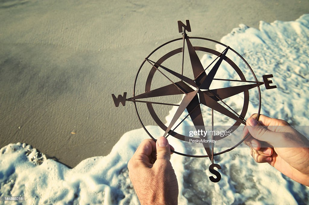 Hands Holding Compass Over Waves Rushing on Beach : Stock Photo
