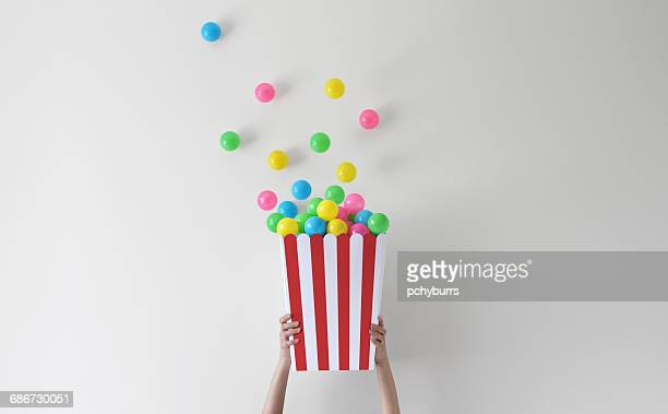 Hands holding conceptual tub of popcorn