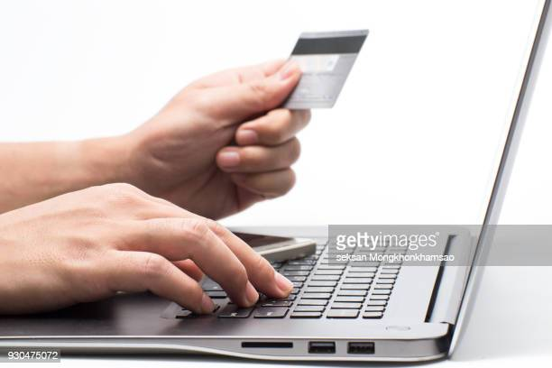 Hands holding credit card and using laptop. Online shopping