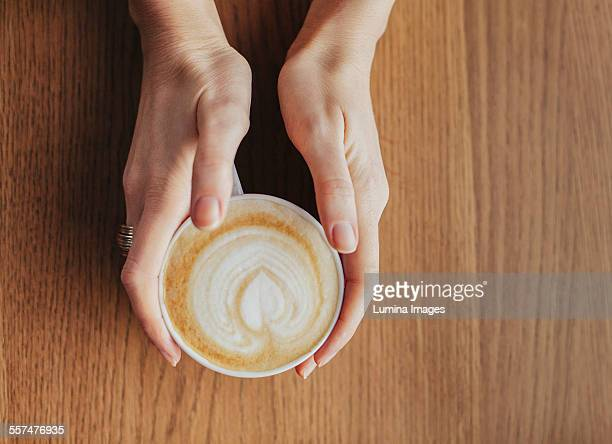 Hands holding cup of coffee with leaf drawn in milk