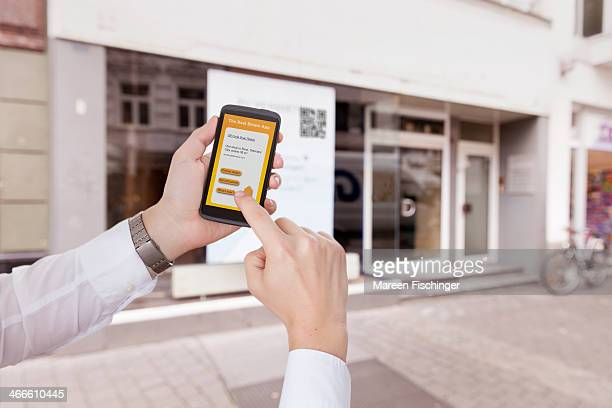 Hands holding device with real estate app in city