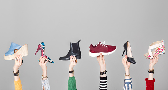 Hands holding different shoes on gray background 1129702431