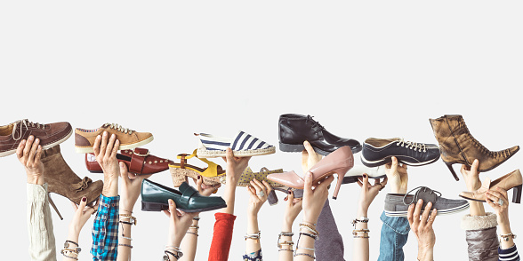 Hands holding different shoes on isolated background 985155706