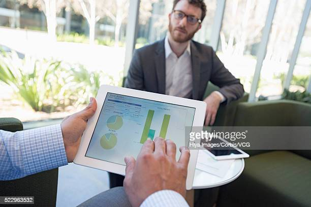 Hands holding digital tablet during business meeting