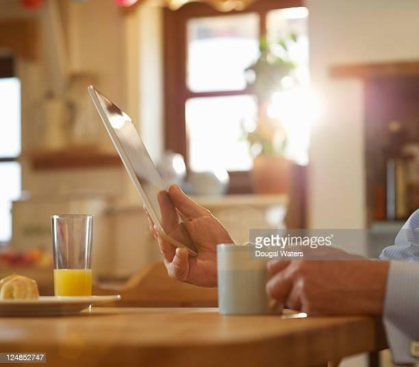 Hands holding digital tablet in kitchen.