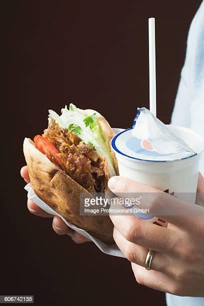 hands holding dner kebab and ayran - dner stock-fotos und bilder
