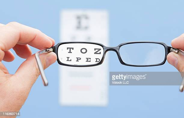 Hands holding eyeglasses in font of eye chart