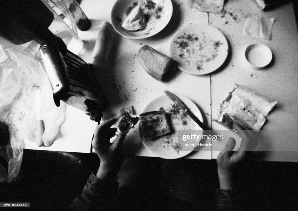 Hands holding food on dirty table, b&w : Stockfoto