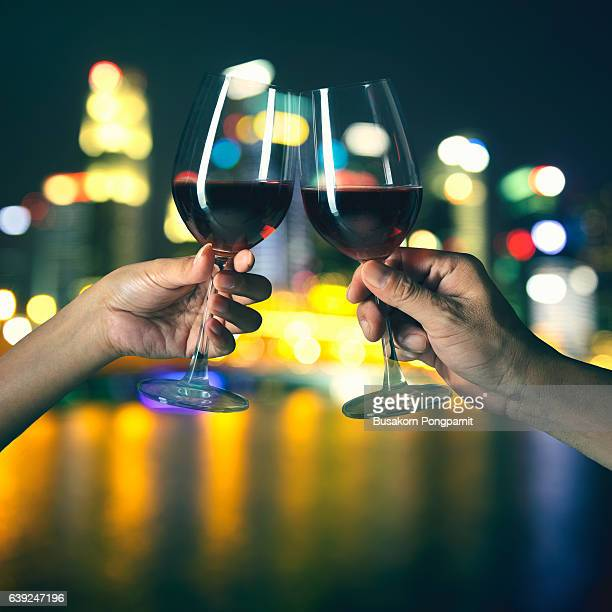 Hands holding glasses of red wine and clicking on the foreground