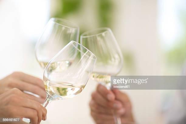 Hands holding glasses of white wine