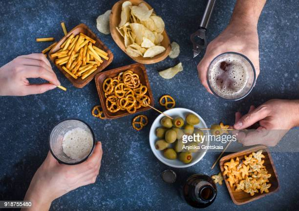 hands holding glasses with beer on a table. couple drinking beer and eating snacks - snack stock pictures, royalty-free photos & images