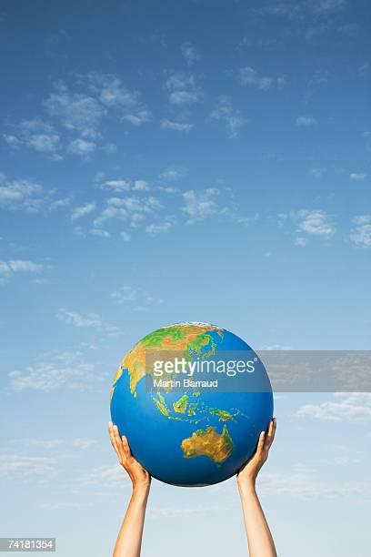 hands holding globe outdoors - alleen één mid volwassen vrouw stockfoto's en -beelden