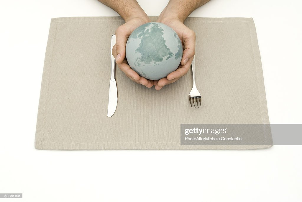 Hands holding globe over placemat and silverware : Stock Photo