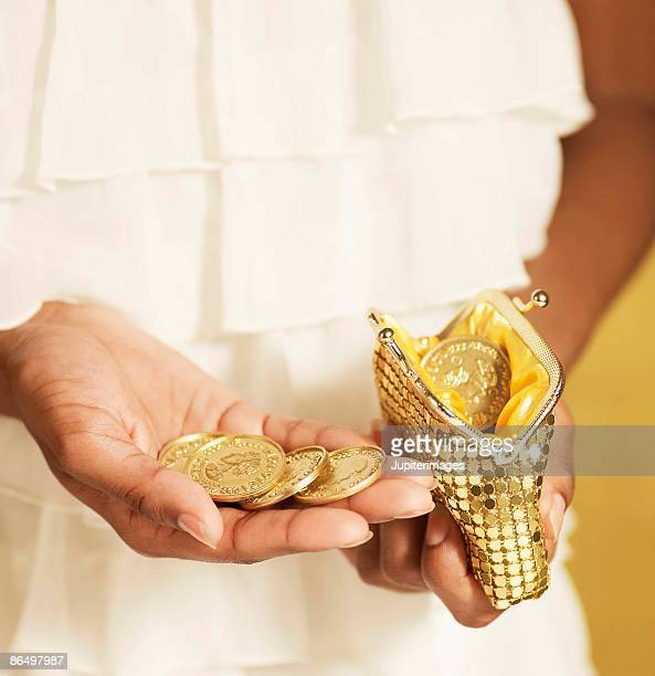 hands holding gold coins and purse - gold purse stock pictures, royalty-free photos & images