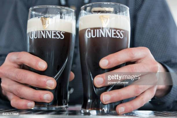 hands holding guinness beer - guinness stock photos and pictures