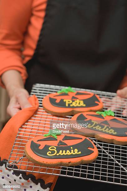 Hands holding Halloween biscuits with names on cake rack