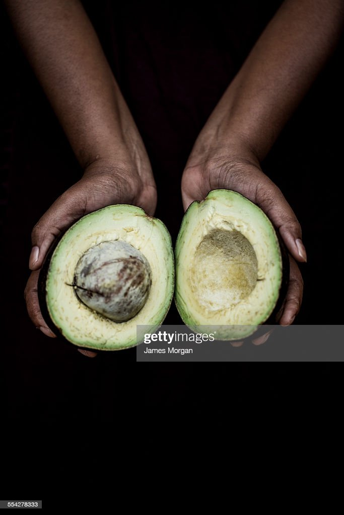 Hands holding halved avocado : Stock Photo