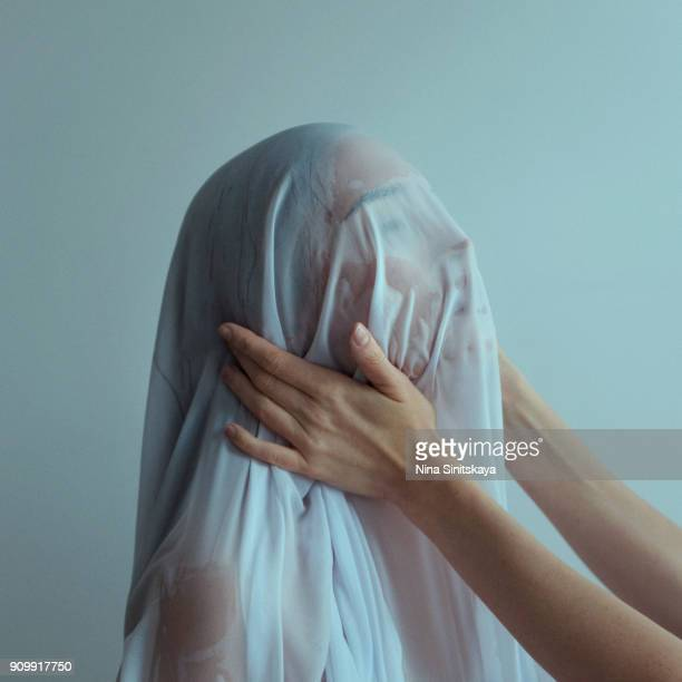 Hands holding head of naked woman covered with wet blue textile