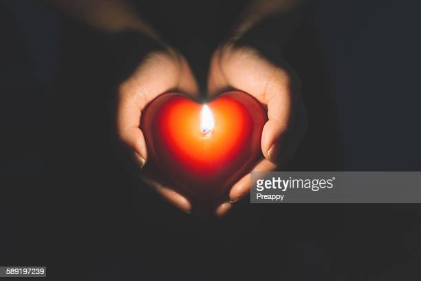 Hands holding heart shape candle