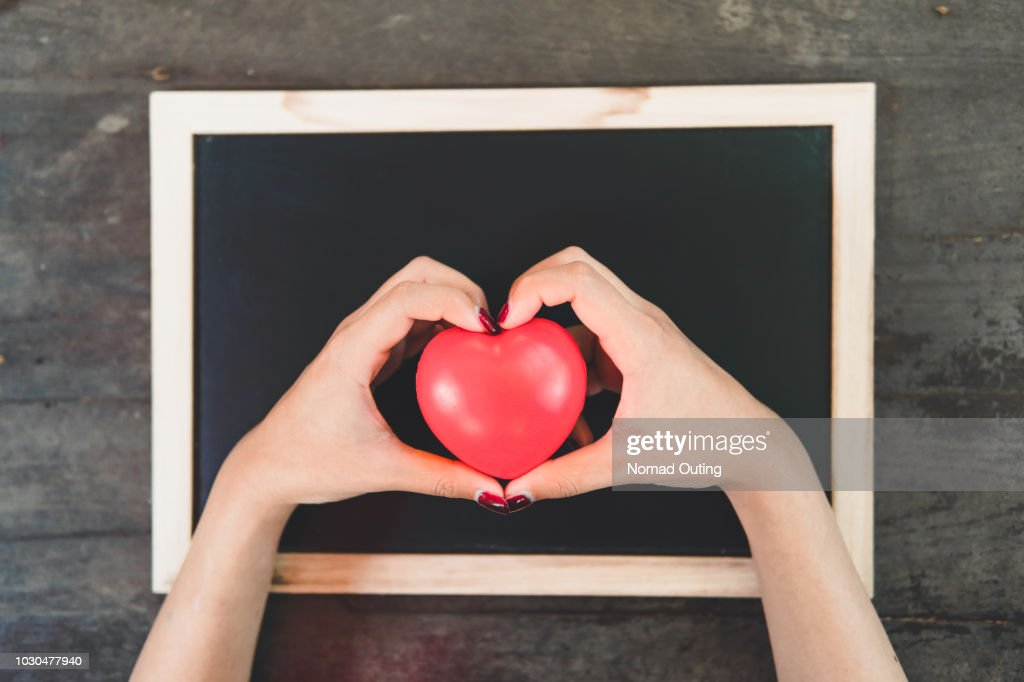hands holding heart shape object over blank blackboard template