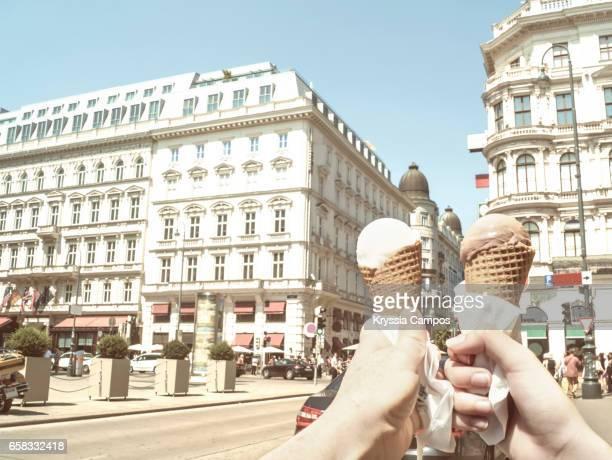 POV hands holding ice cream cones at streets