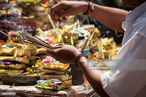 Hands holding incense and religious gifts