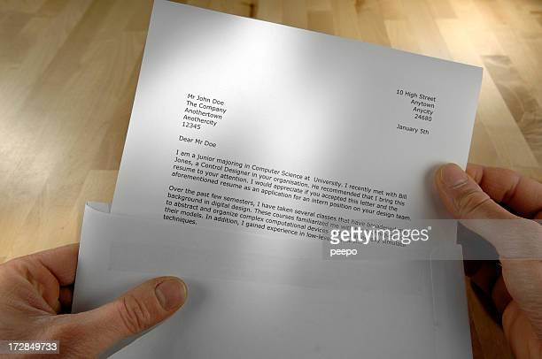 pov of hands holding job application letter - bericht stockfoto's en -beelden