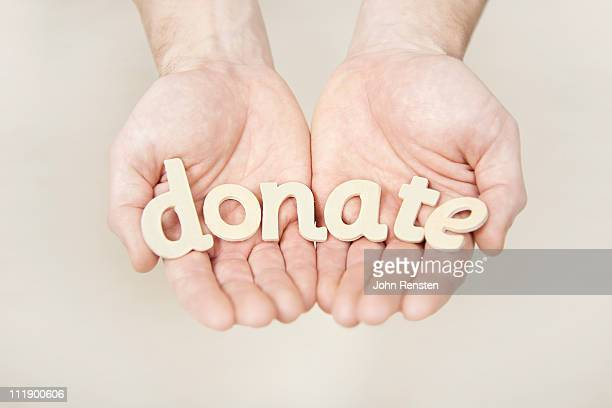 hands holding letters spelling words - donation stock photos and pictures