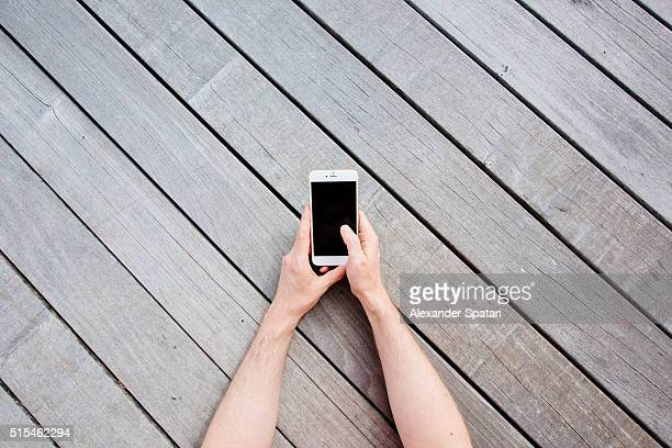Hands holding mobile phone against wooden background