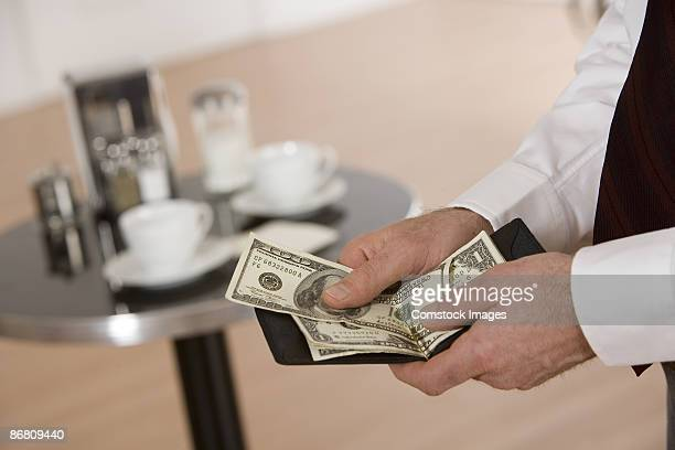 Hands holding money and wallet in restaurant