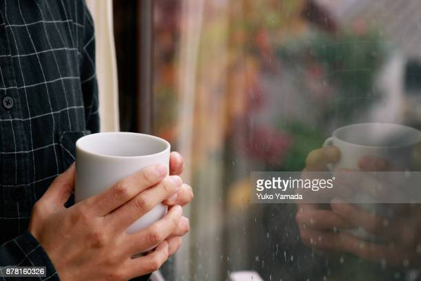 Hands Holding Mug - Rainy Day by the Window