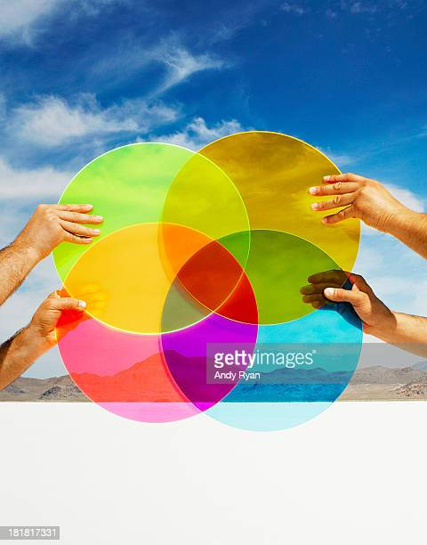 Hands holding multi-colored discs in landscape.