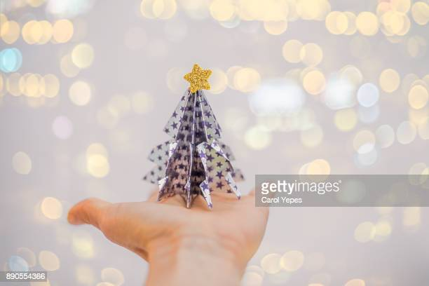hands holding origami christmas tree in  glow background