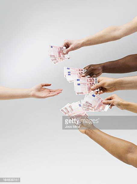 Hands holding out money, one hand receiving