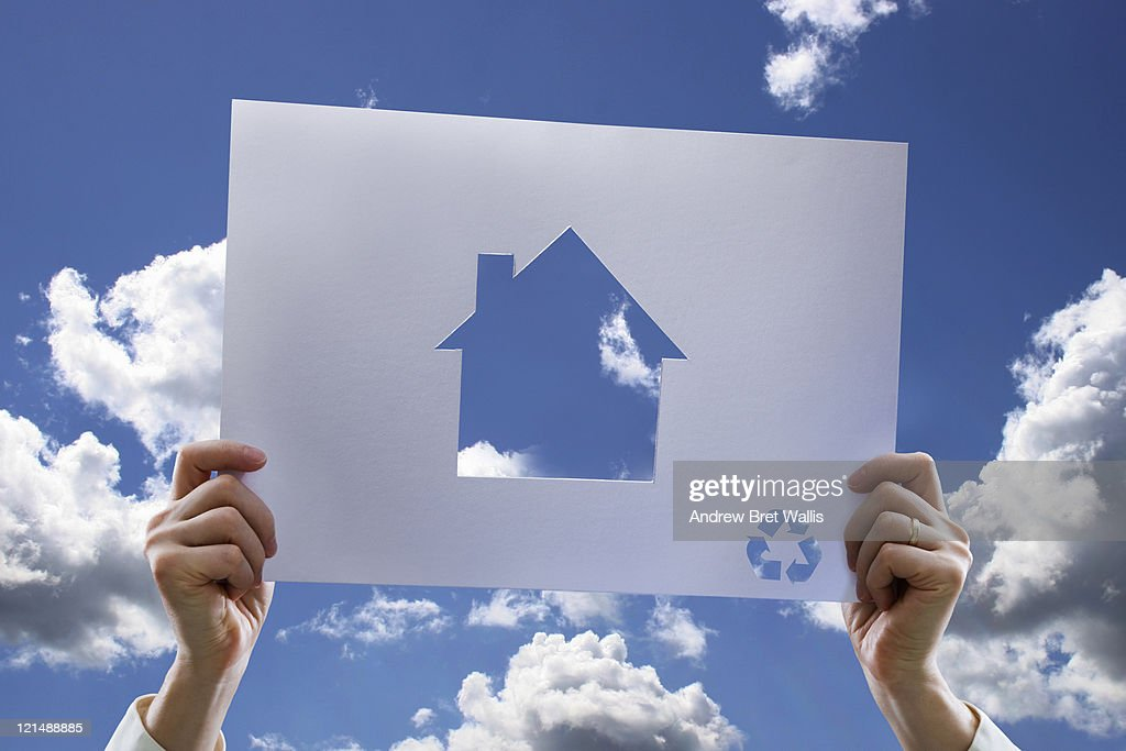 Hands holding paper cut-out of eco house : Foto de stock