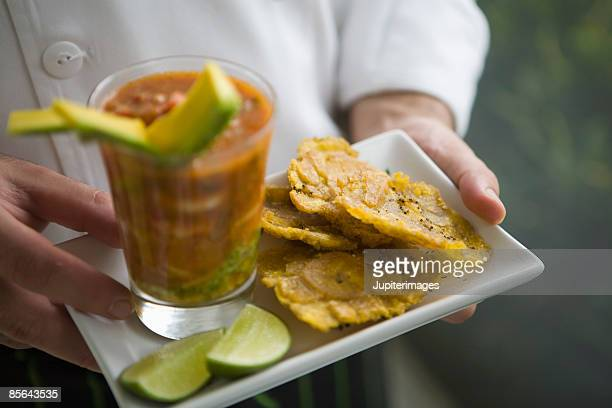 Hands holding patacones fried plantains with seafood cocktail