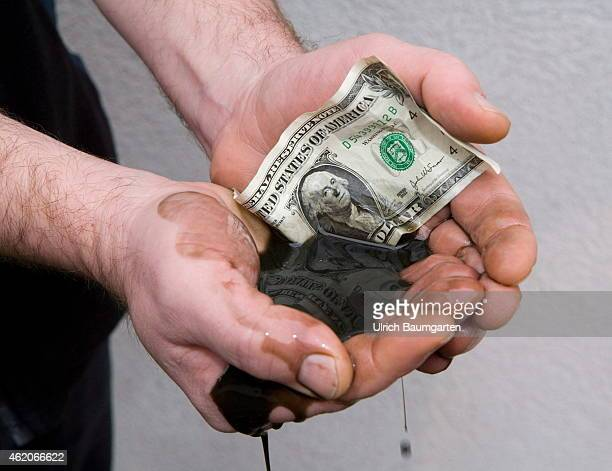 Hands holding petroleum and a 1 Dollar banknote Symbol photo on the topics of petroleum petroleum prices global economy energy etc on January 23...