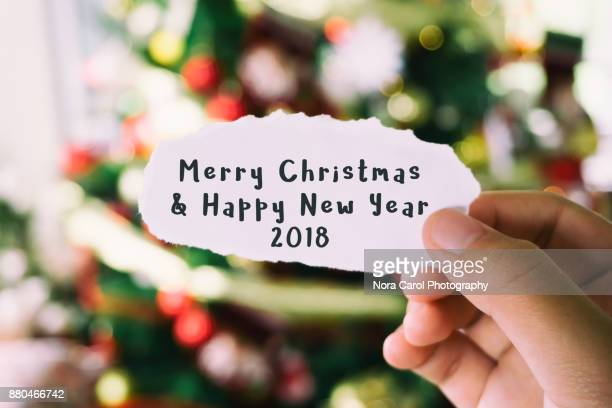 hands holding piece of paper with text merry christmas and happy new year with christmas tree background - christmas banner stock photos and pictures