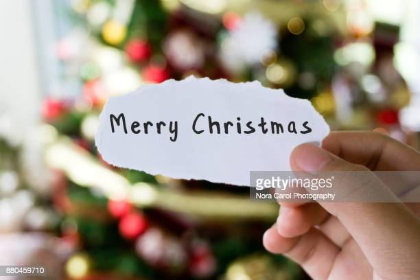 hands holding piece of paper with text merry christmas with christmas tree background - christmas banner stock photos and pictures