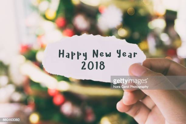Hands Holding Piece of Paper With Word Happy New Year 2018 Christmas Tree Background