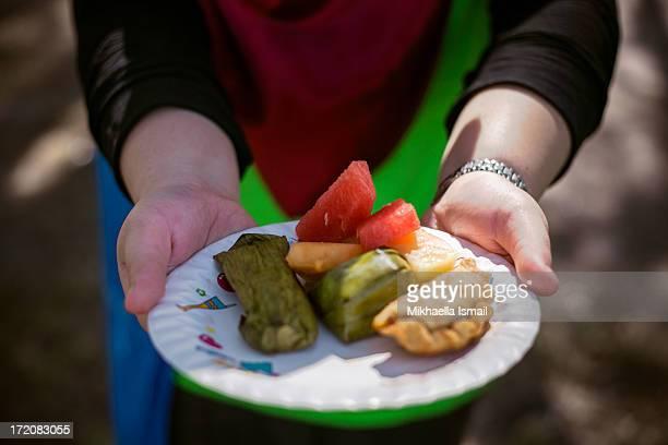 Hands holding Plate of Malaysian Dessert
