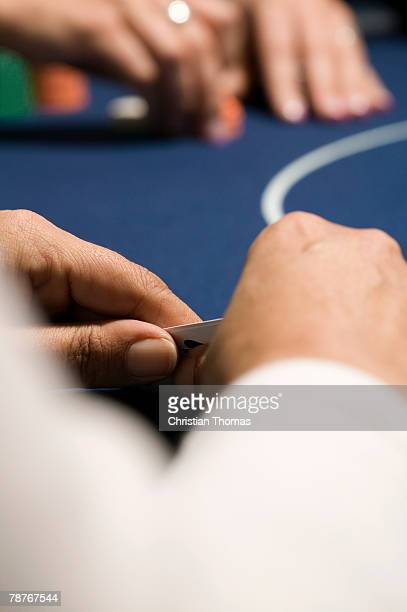 Hands holding playing cards at casino table