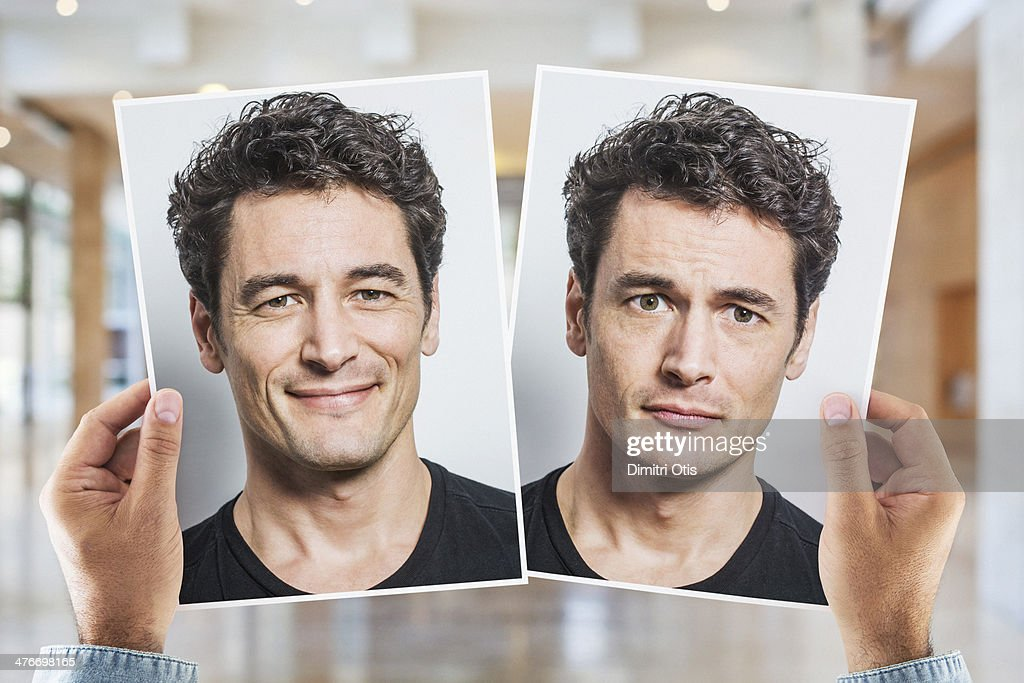 Hands holding portrait of man being happy and sad : Stock Photo