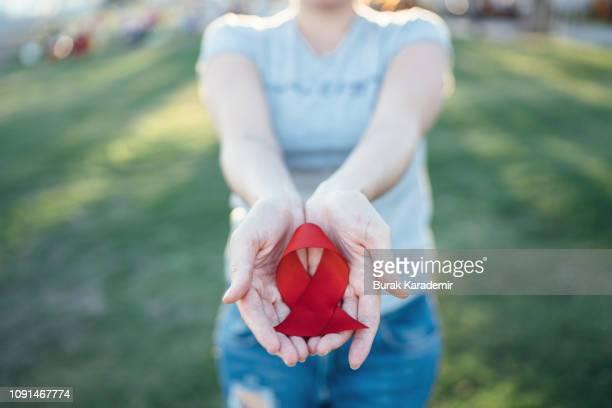 hands holding red aids awareness ribbon - aids stock-fotos und bilder