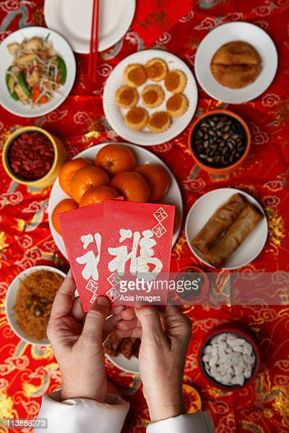 Hands holding red envelopes (Hong Bao) over table with Chinese food.