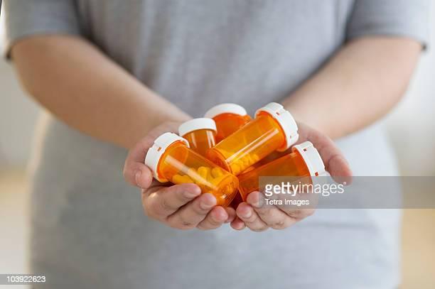 Hands holding several bottles of prescription medication