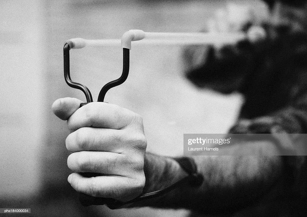 Hands holding sling shot, close-up, b&w : Stockfoto